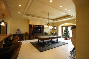 large living area with pool table at the center and hanging chandelier over it