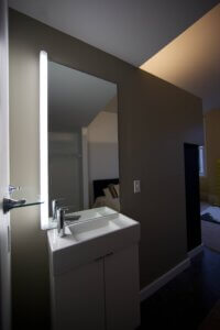 bathroom mirror and sink illuminated by LED lighting