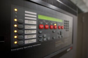 closeup photo of black fire alarm system with buttons and lights