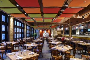 restaurant dining area with square wooden tables and ceiling tiles with spotlights