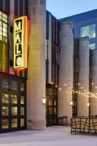 Malo restaurant sign at night suspended above building entrance