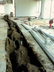 dirt trench inside a construction project with piping laid beside it