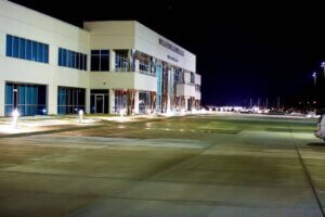 exterior of large white and chrome building at night with lit walkway beside it