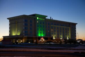 exterior of Holiday Inn & Suites at night, with green lights illuminating the side of the building