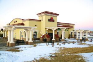 exterior photo of yellow Applebees building with snow outside