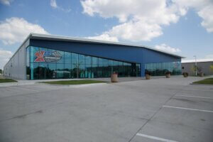 exterior shot of glass Karl Performance building with blue sky and clouds behind