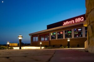 edterior photo of Jethro's BBQ building and neon sign at night