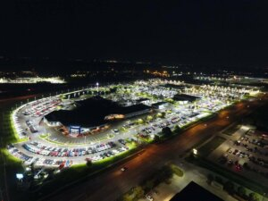 overhead photo of car dealership at night with parking lot lit by LED lights