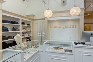 interior photo of jewelry counter with crystal chandeliers and a sign that says blond genius