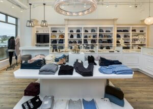 retail store interior displaying clothing on tables with large overhead chandelier