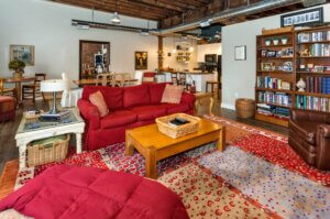 apartment living room with hanging light fixtures and red couches with patterned rug