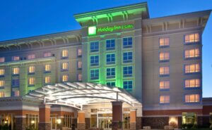 exterior of Holiday Inn & Suites with green light illuminating the front