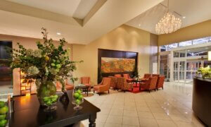 lobby area with a large crystal chandelier, red armchairs, and a table with greenery