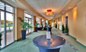 carpeted hallway with large overhead light fixtures and black marble tables throughout