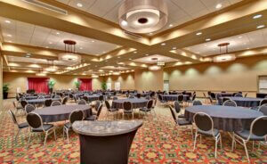 large ballroom with round tables set up and overhead lighting