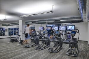 treadmills and ellipticals facing a wall of televisions