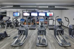gym cardio equipment facing a wall of televisions